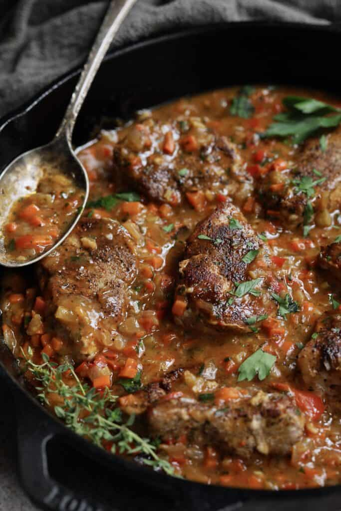 Photo of Cajun-Smothered Pork Medallions in cast iron skillet garnished with thyme sprigs.