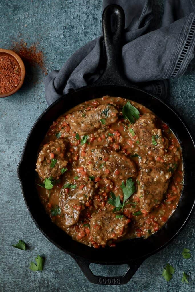Cajun-Smothered Pork Medallions - Overhead shot on blue background garnished with parsley