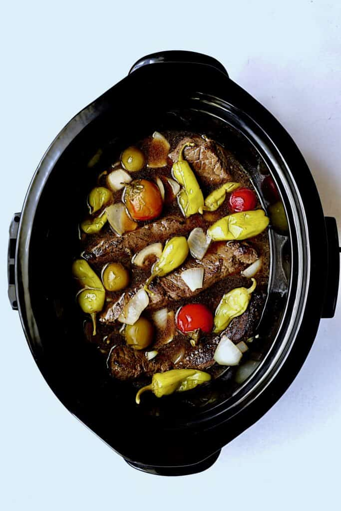 Overhead shot of short ribs in slow cooker before cooking