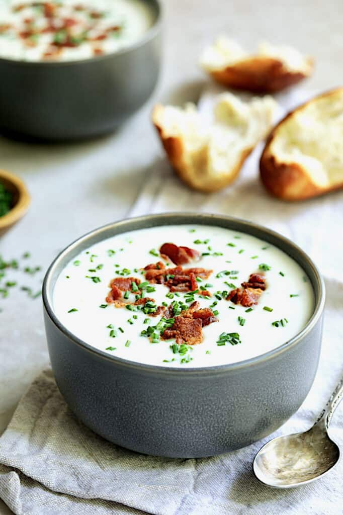 Potato and Leek Soup with White Cheddar - Straight-on shot of soup in gray bowl with broken bread in the background