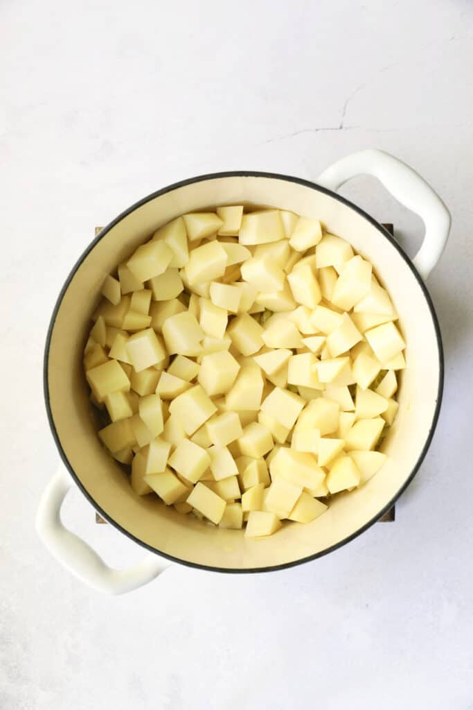 Overhead shot of cubed potatoes in white Dutch oven