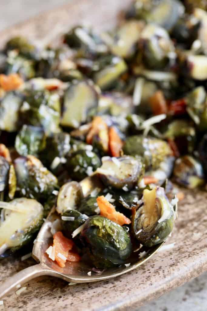 Close-up photo of Roasted Purple Brussels Sprouts with Bacon and Parmesan on serving spoon.