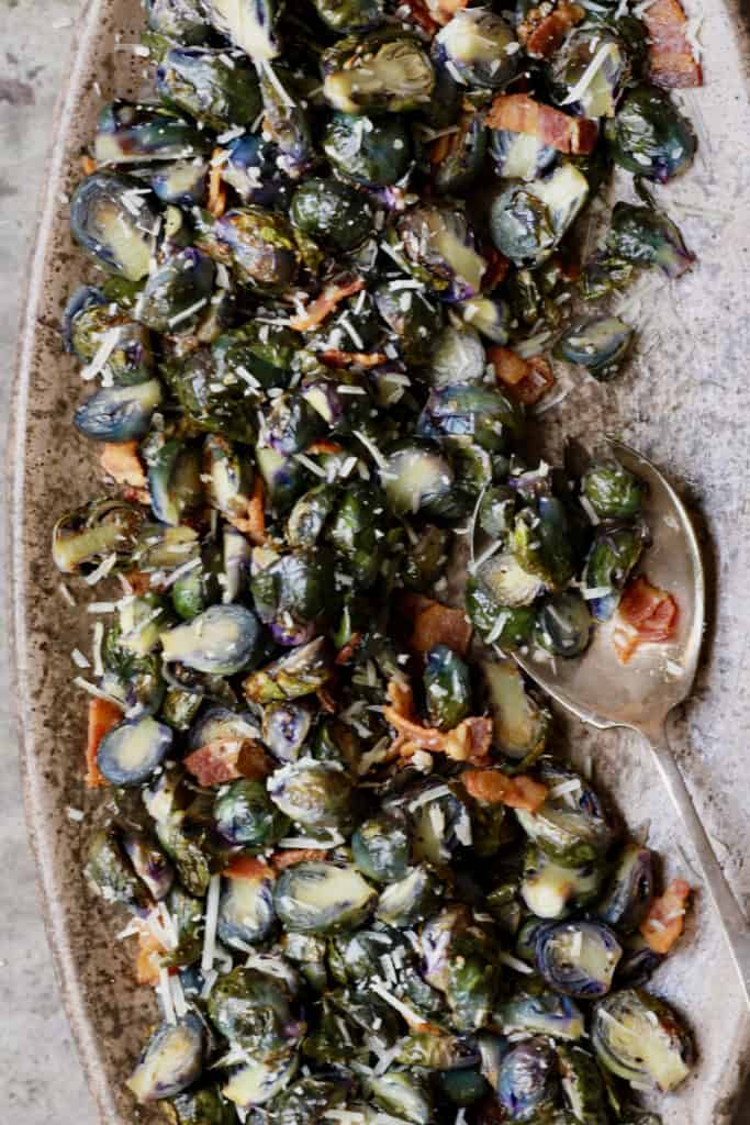 Close-up photo of Roasted Purple Brussels Sprouts with Bacon and Parmesan on brown platter.