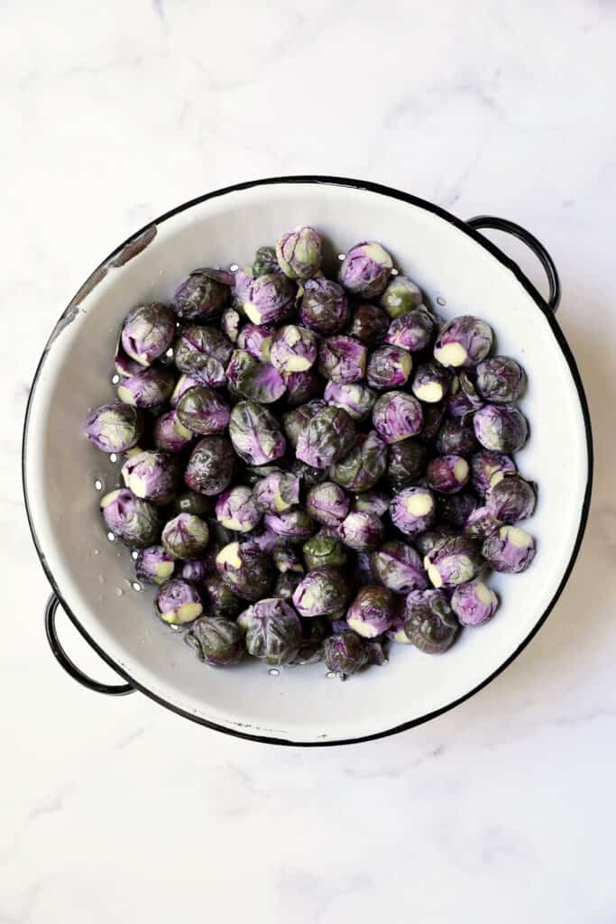 Overhead shot of purple Brussels sprouts in white colander