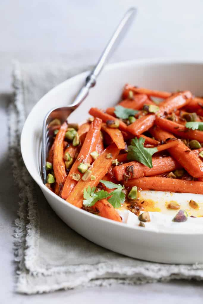 Spiced Roasted Carrots with Pistachios and Labneh - Straight-on shot in white rimmed dish with serving fork
