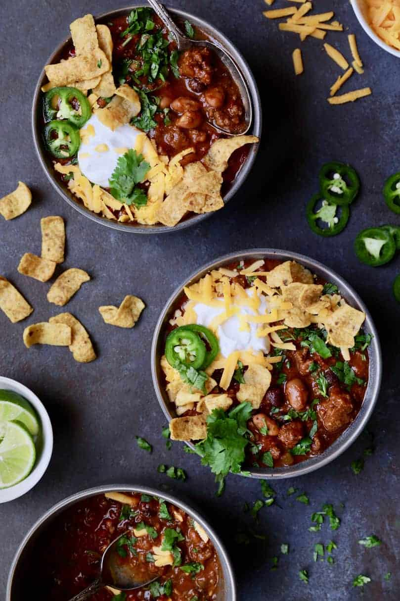 Chipotle Beef and Bean Chili - Overhead hero shot of two full bowls with garnishes