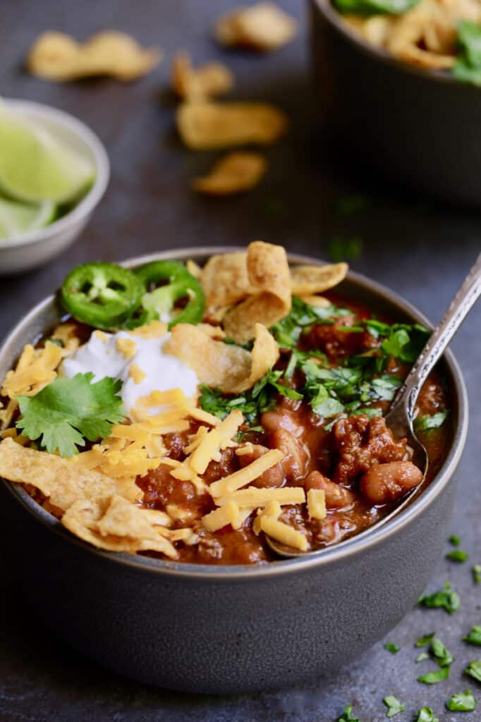 Chipotle Beef and Bean Chili - Straight-on close-up shot of chili in gray bowl with garnishes