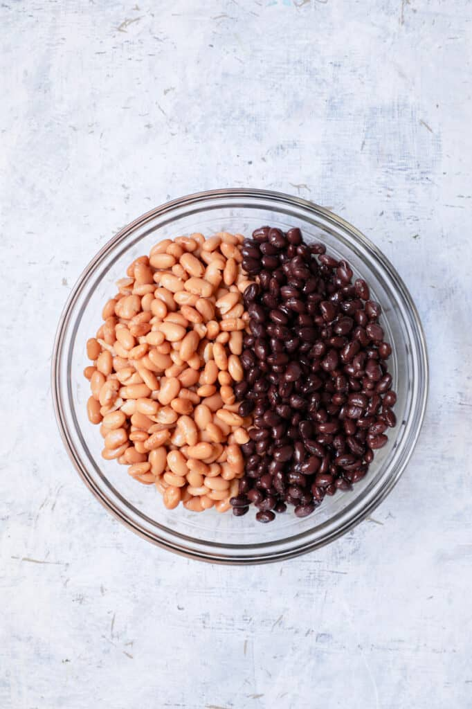 Overhead shot of pinto and black beans in glass bowl