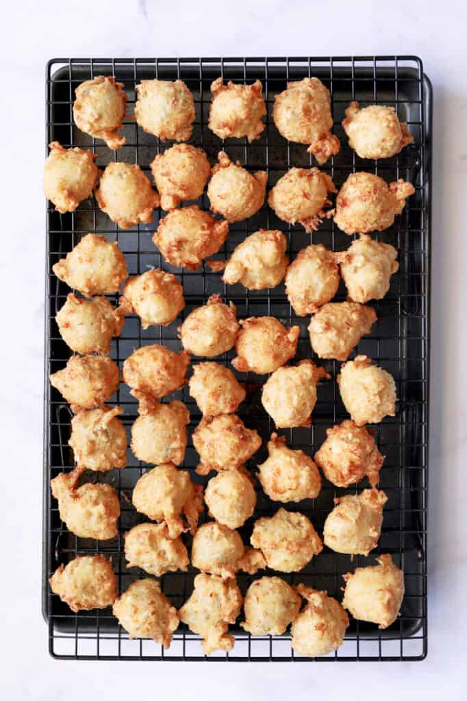 Photo of fried Crab and Artichoke Beignets on cooling rack set over a rimmed sheet pan.