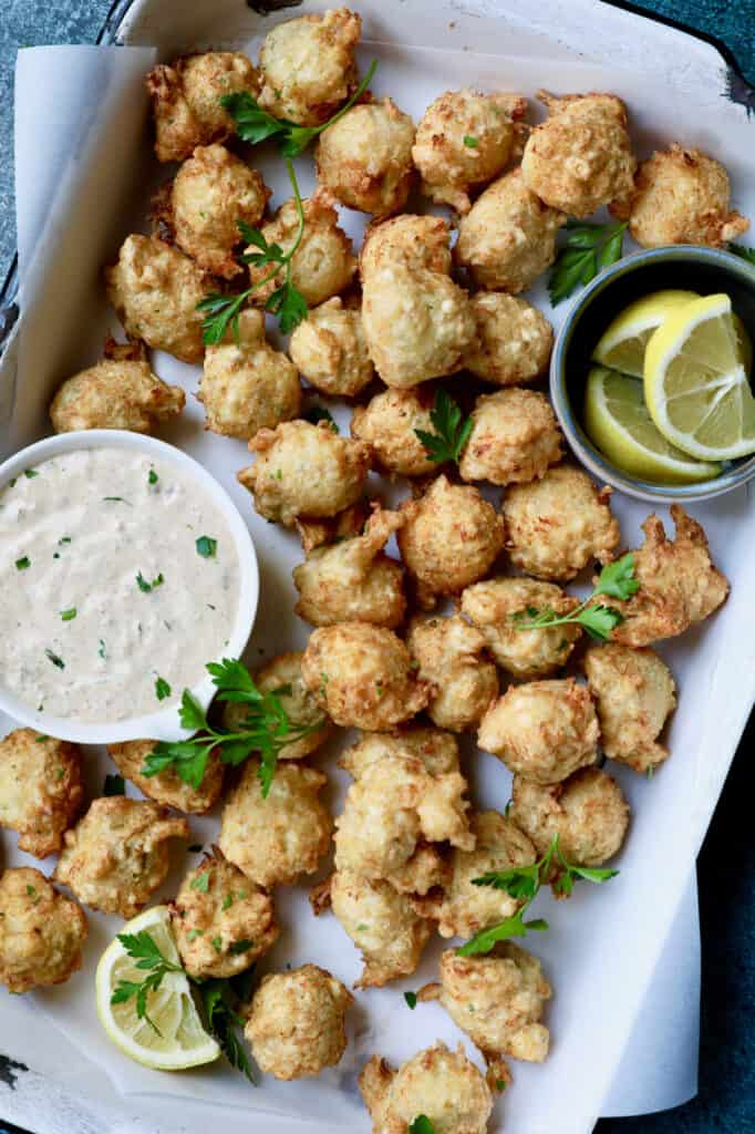 Photo of Crab and Artichoke Beignets with Jalapeno Remoulade  in white pan with lemon wedges.