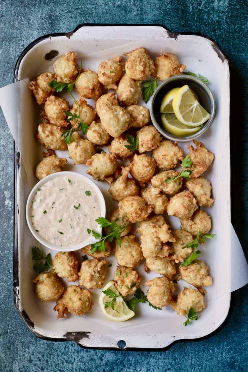 Crab and Artichoke Beignets with Jalapeno Remoulade - Overhead hero shot of beignets in white distressed pan garnished with parsley and lemon