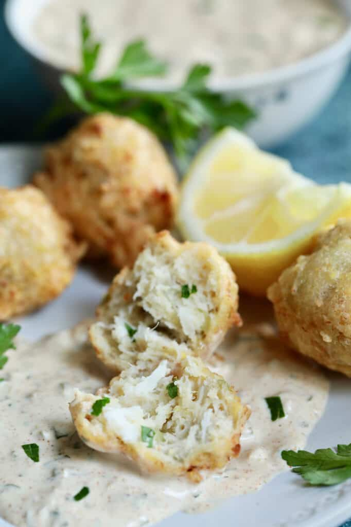 Close-up photo of Crab and Artichoke Beignets with Jalapeno Remoulade showing interior of beignet garnished with lemon and parsley.