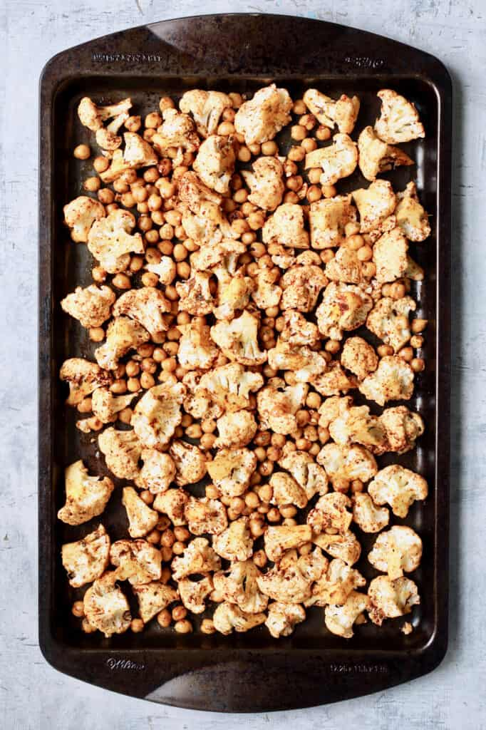 Overhead shot of cauliflower and chickpeas on baking sheet before roasting