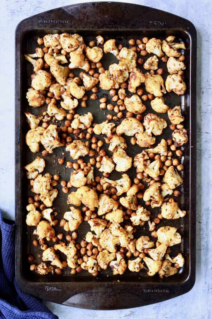Overhead shot of cauliflower and chickpeas on baking sheet after roasting