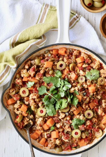 Cuban-Style Turkey Picadillo with Sweet Potatoes - Overhead hero shot of dish in white cast iron skillet