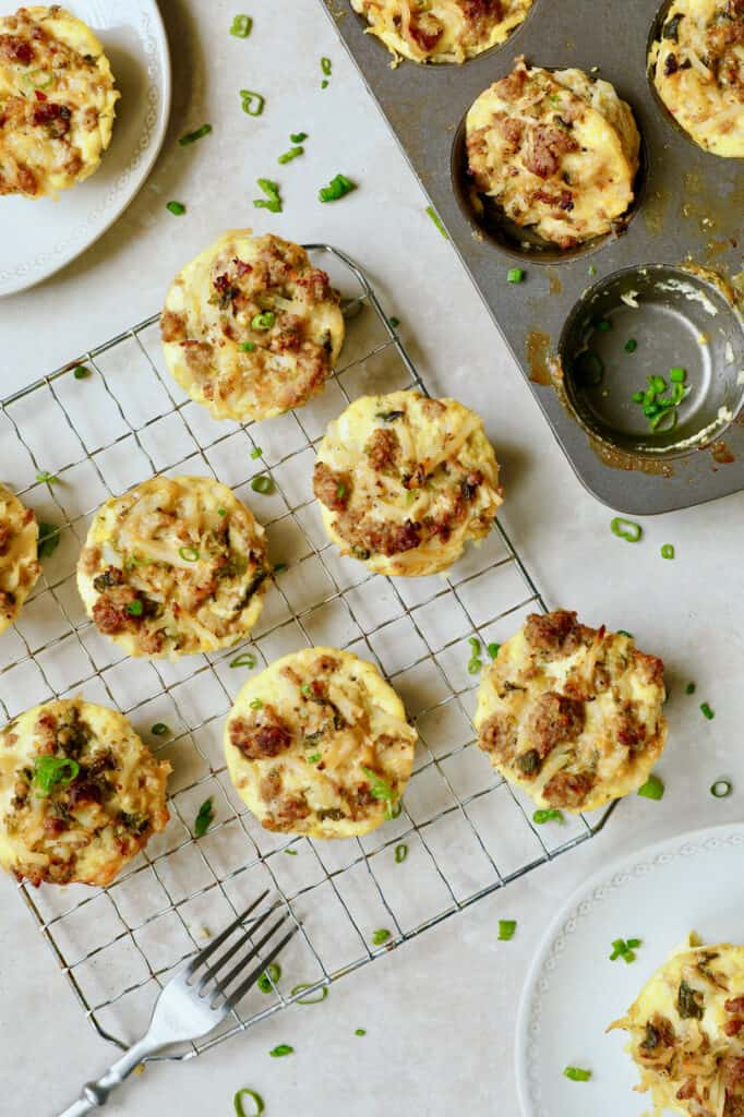 Overhead photo of Hash Brown Breakfast Muffins with Poblano Peppers and Gouda Cheese on cooling rack with some still in muffin pan and some on plates.