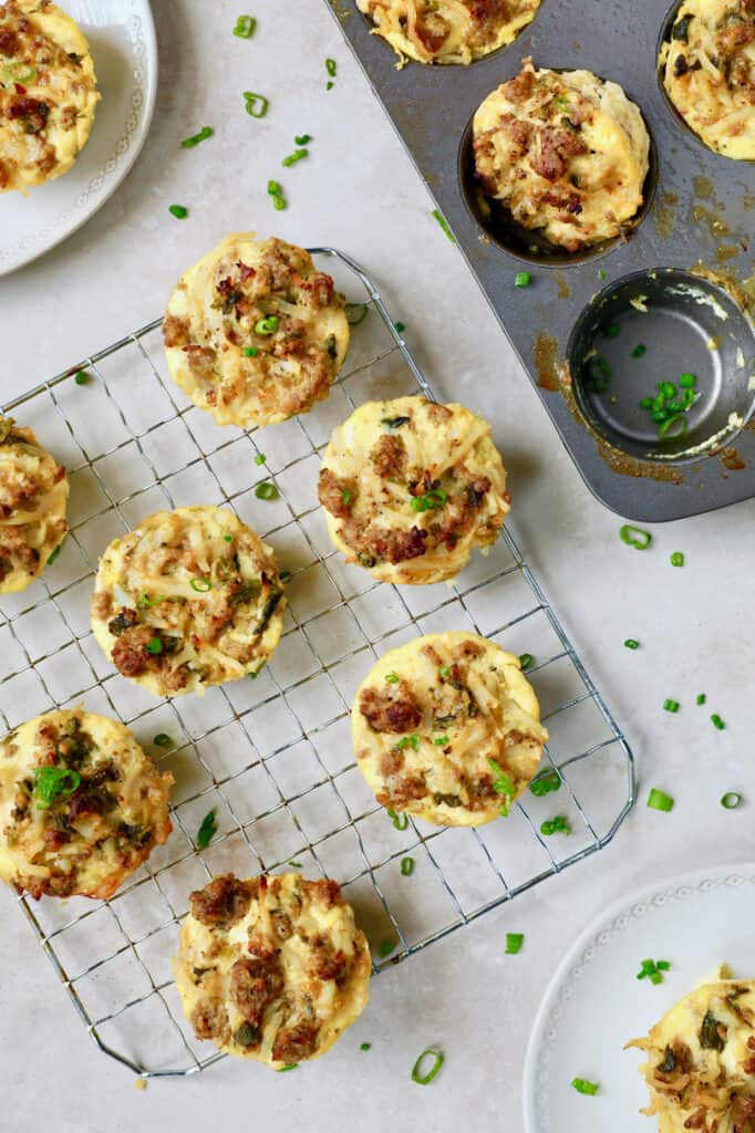 Photo of Hash Brown Breakfast Muffins with Poblano Peppers and Gouda Cheese on cooling rack garnished with chives.