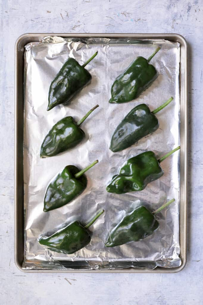 Photo of fresh Poblanos on foil-lined baking sheet about to be roasted.
