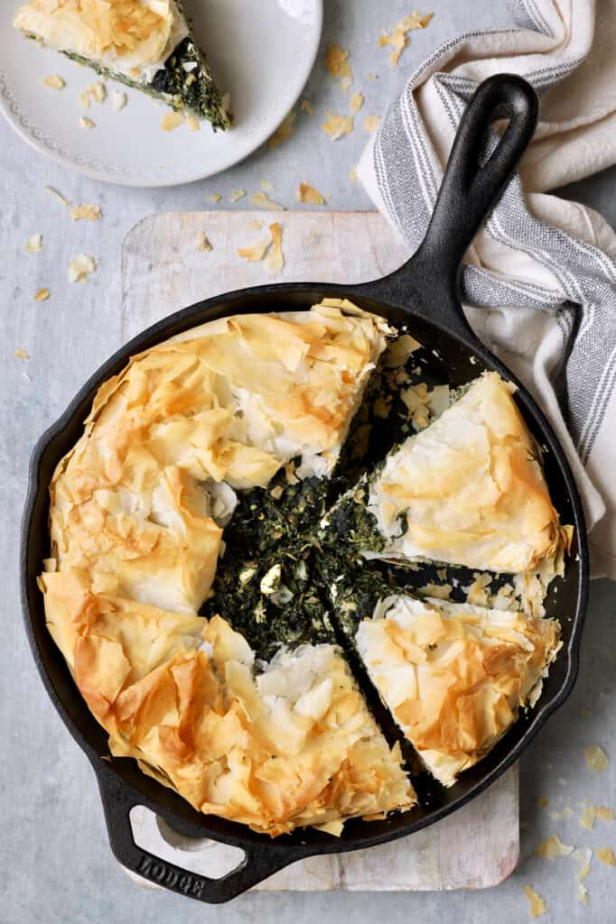 Photo of Skillet Spanakopita (Greek Spinach and Feta Pie) cast iron skillet with gray striped towel.