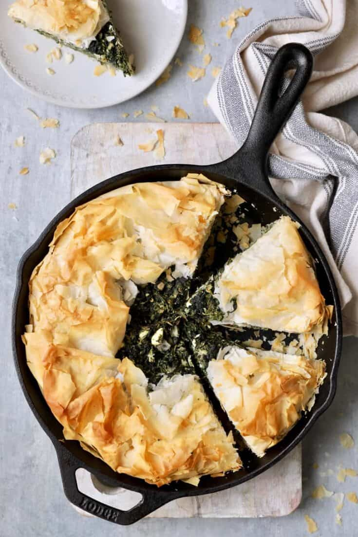 Skillet Spanakopita (Greek Spinach and Feta Pie) - Overhead shot in cast iron skillet with gray striped towel