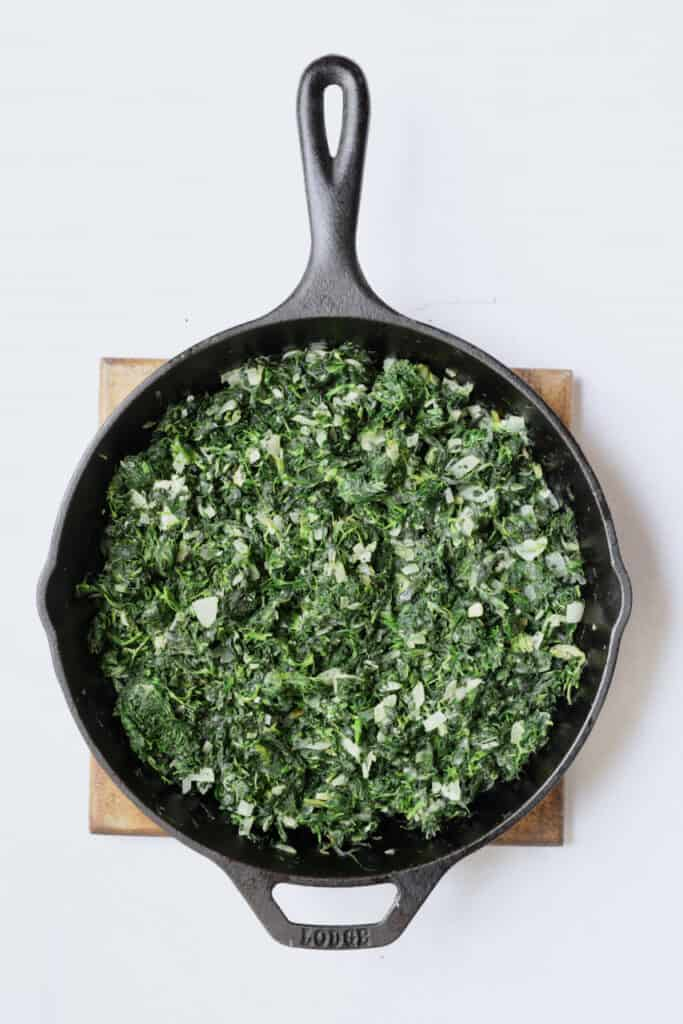 Photo of spinach and onions being cooked in cast iron skillet.