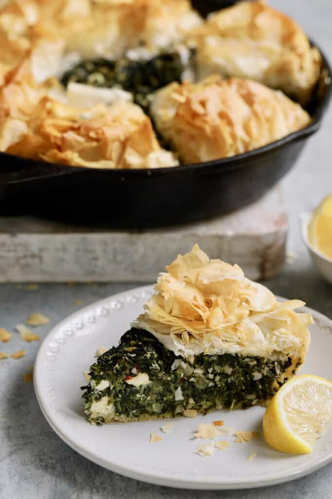 Photo of one slice of Skillet Spanakopita (Greek Spinach and Feta Pie) on small white plate with rest of the pie in the background.
