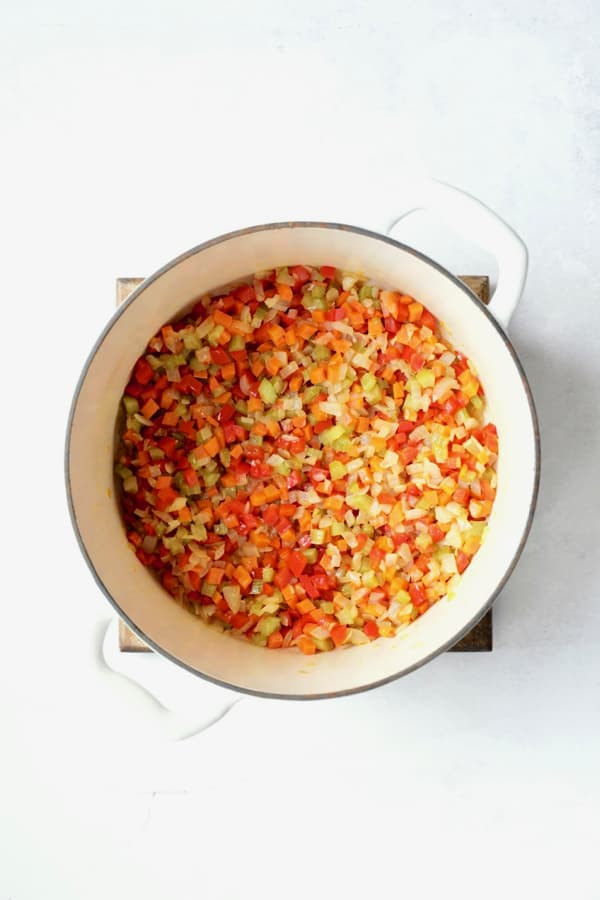Photo of vegetables being cooked in white Dutch oven.