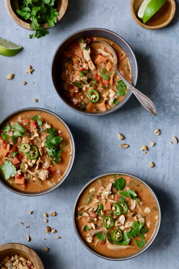 Photo of Spicy Chicken Sweet Potato and Peanut Soup in gray bowls on blue background garnished with cilantro peanuts and lime wedges.