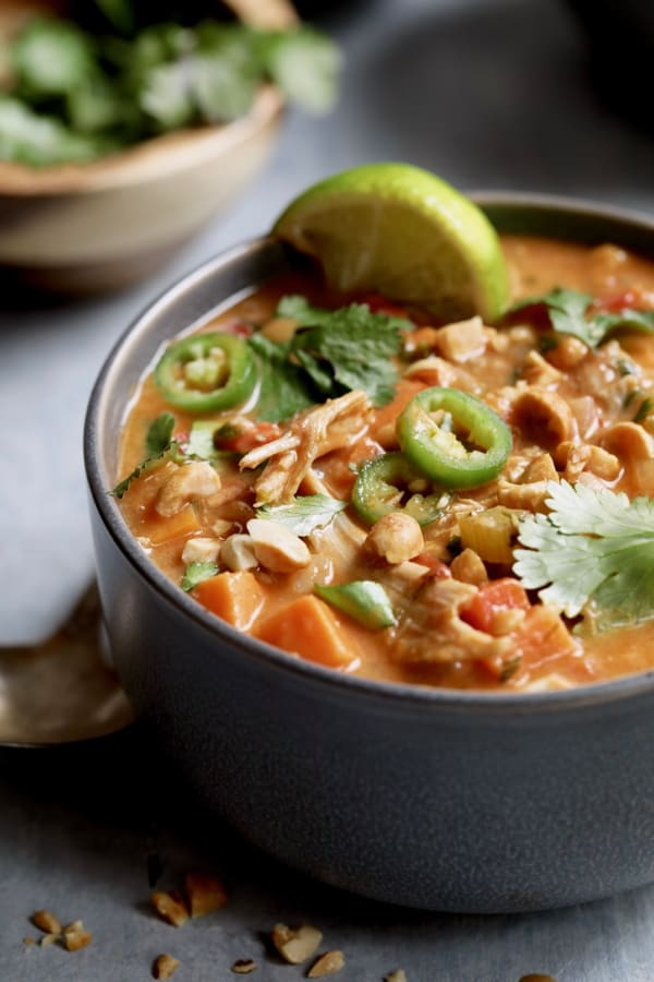 Photo of Spicy Chicken Sweet Potato and Peanut Soup in gray bowl garnished with cilantro and green chiles.