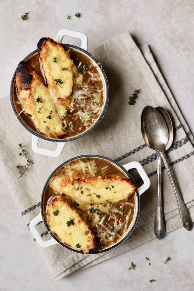 Photo of French Onion Soup with cheesy croutons on beige and black-striped napkin.