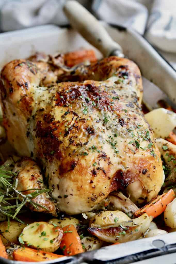 Close-up photo of Garlic Herb Butter Roast Chicken with Root Vegetables in white roasting pan.