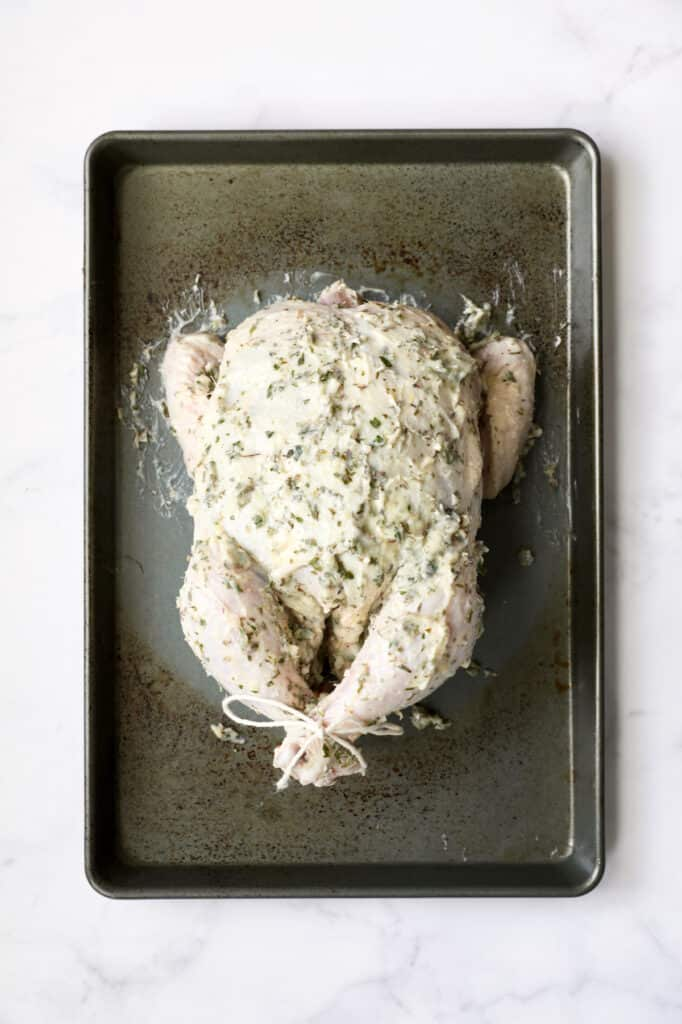 Photo of uncooked whole chicken rubbed with butter on baking sheet.