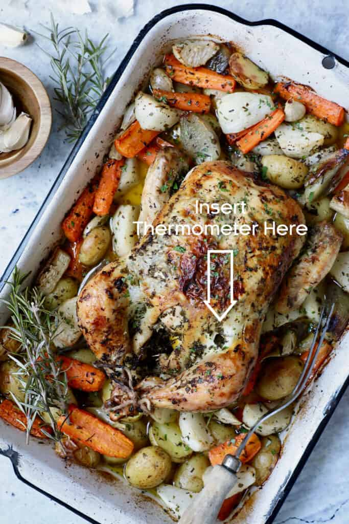 Photo of Garlic Herb Roast Chicken with Root Vegetables garnished with rosemary showing where to test for doneness.
