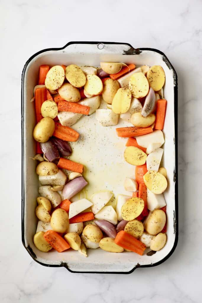 Photo of uncooked root vegetables in white roasting pan.