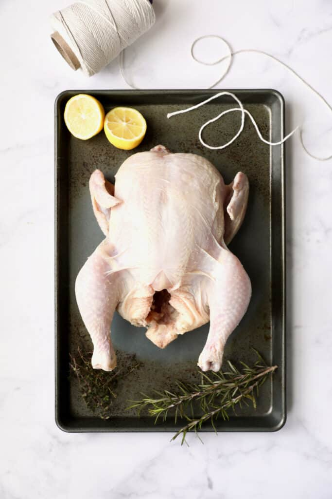 Photo of uncooked whole chicken on baking sheet with butcher's twine, lemon halves and herb sprigs.