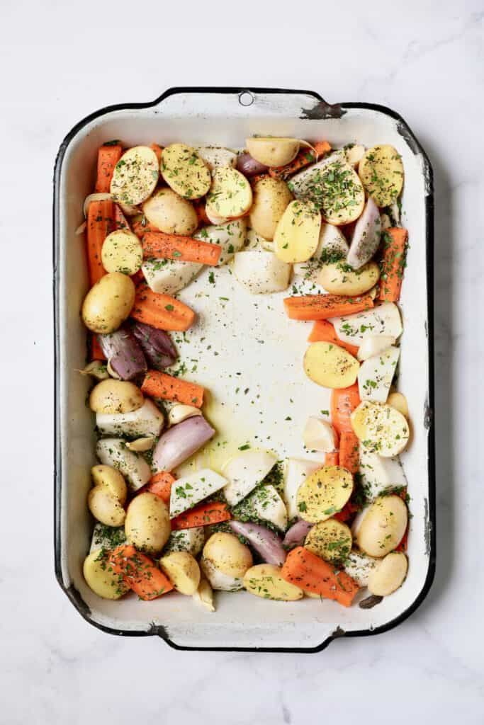 Photo of uncooked root vegetables in white roasting pan sprinkled with fresh herbs.