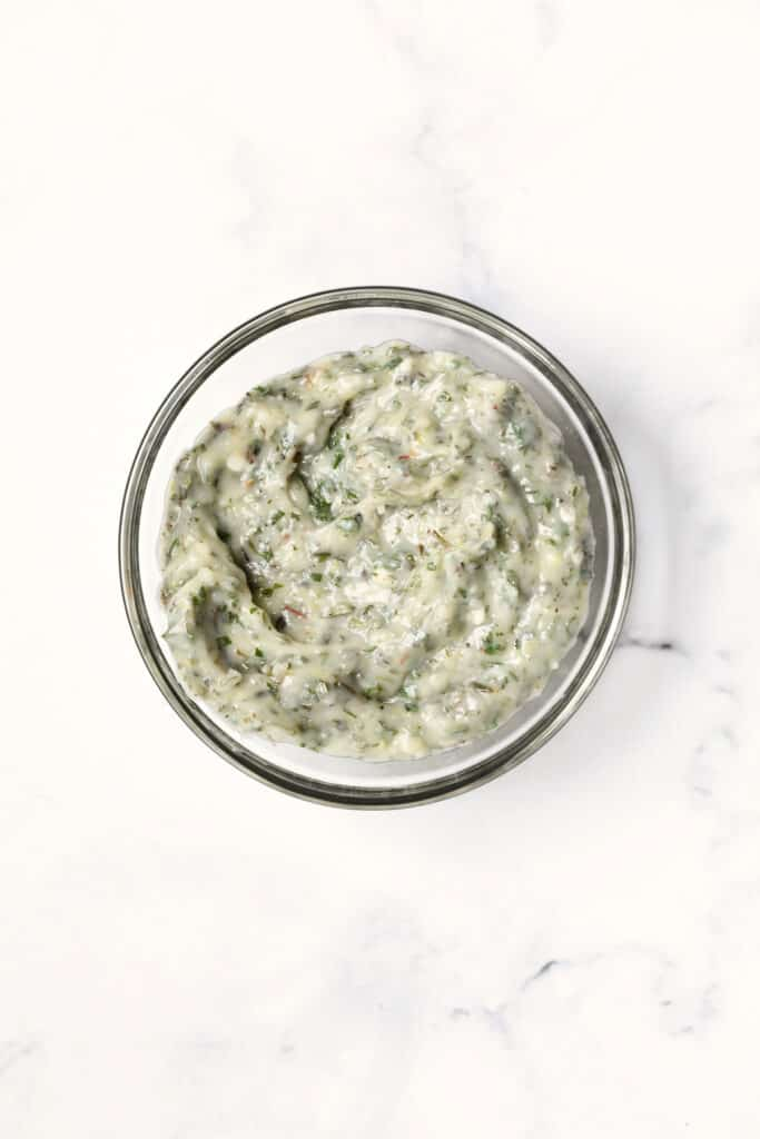 Photo of Garlic Herb Butter in glass bowl on white background.
