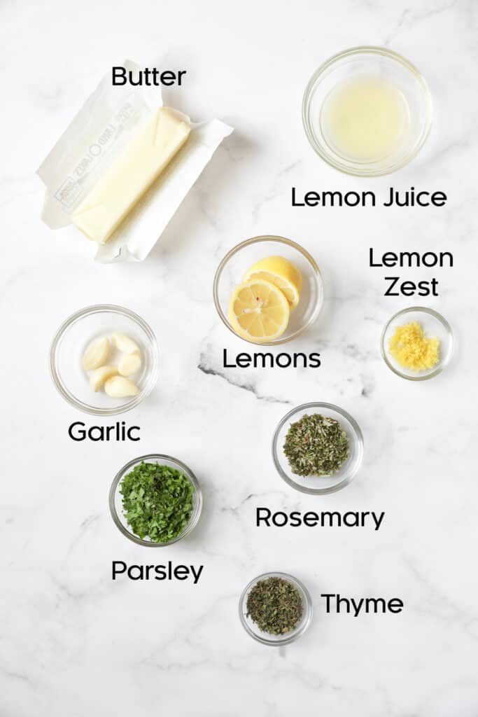 Ingredients for garlic herb butter in glass bowls on marble background.