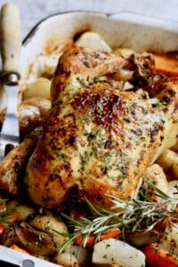 Photo of Garlic Herb Butter Roast Chicken with Root Vegetables with meat fork nearby.