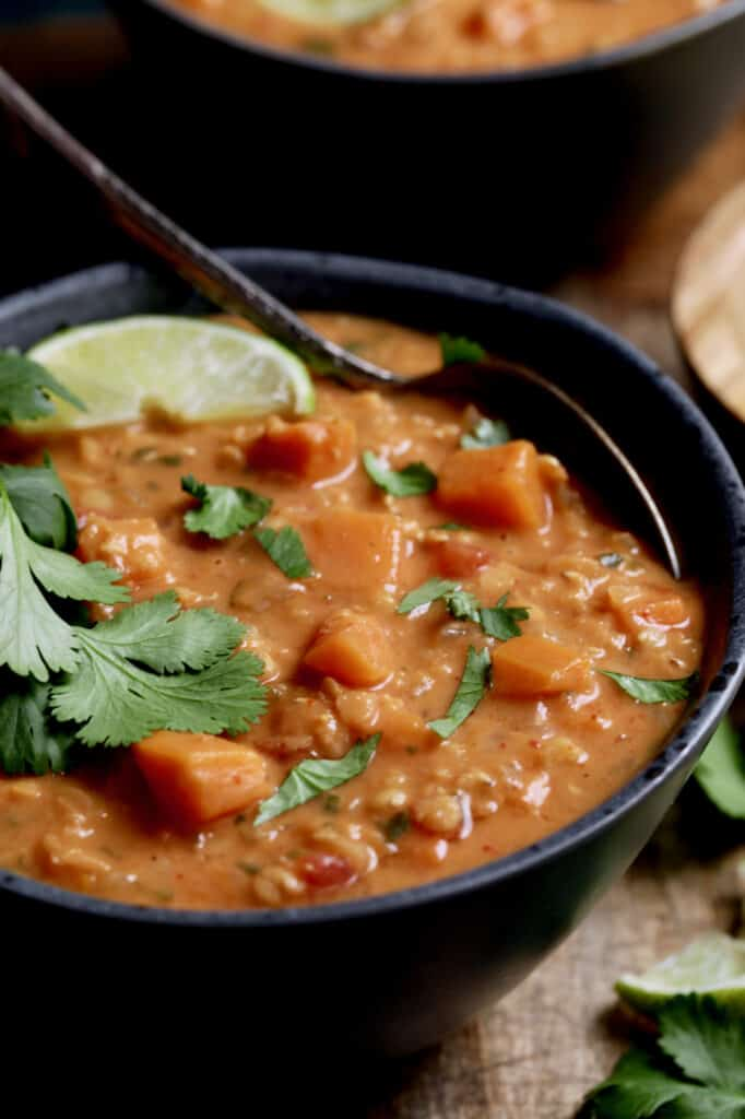 Close-up photo of Thai Red Curry Sweet Potato and Lentil Soup in gray bowl garnished with lime and cilantro.