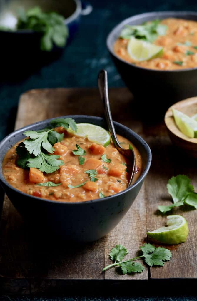 Photo of Thai Red Curry Sweet Potato and Lentil Soup in gray bowl on wood surface garnished with lime and cilantro.