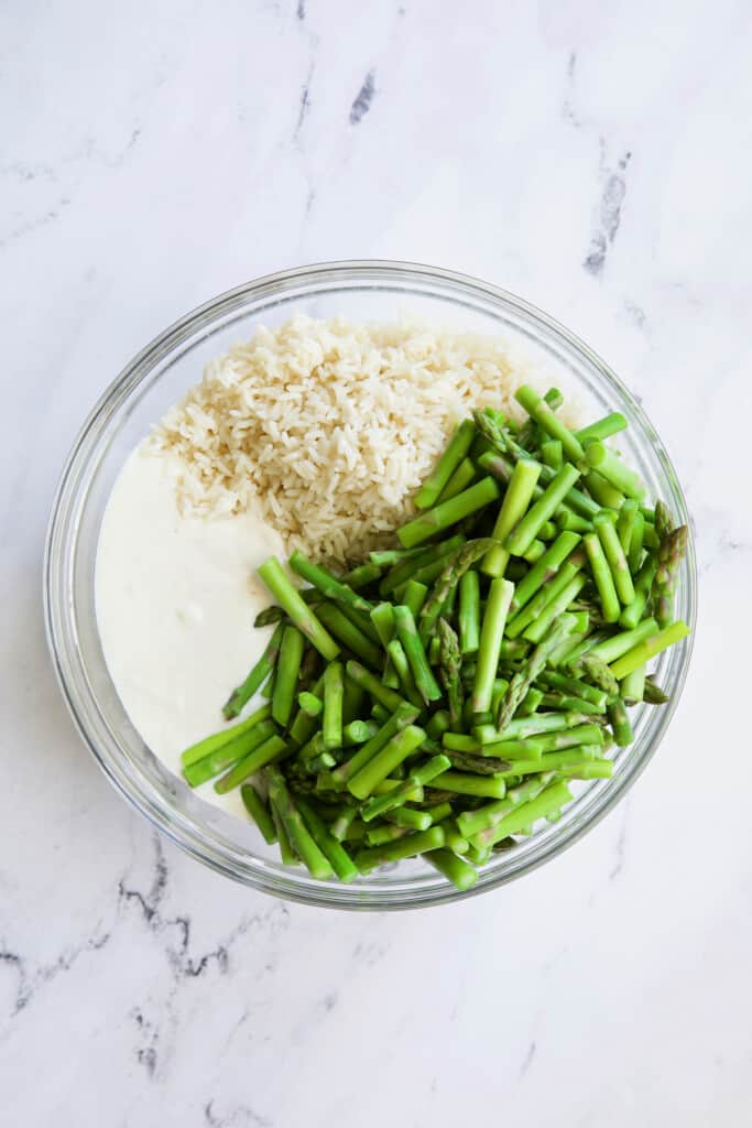 Photo of cream sauce, rice and blanched asparagus in glass bowl.