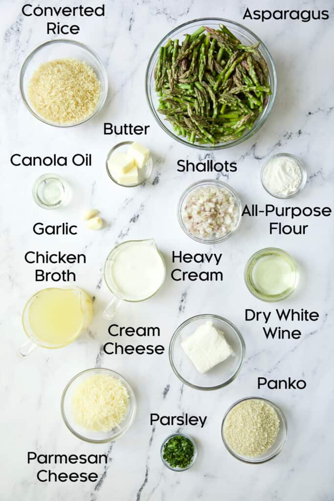 Photo of ingredients for Creamy Asparagus and Rice Casserole in glass bowls on marble background.