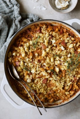 Photo of Easy Weeknight Chicken and Sausage Cassoulet with gray napkin and serving utensils.