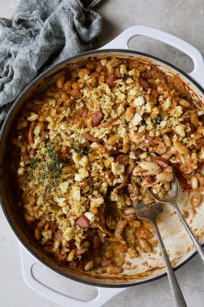 Photo of Easy Weeknight Chicken and Sausage Cassoulet after some has been served with serving utensils.
