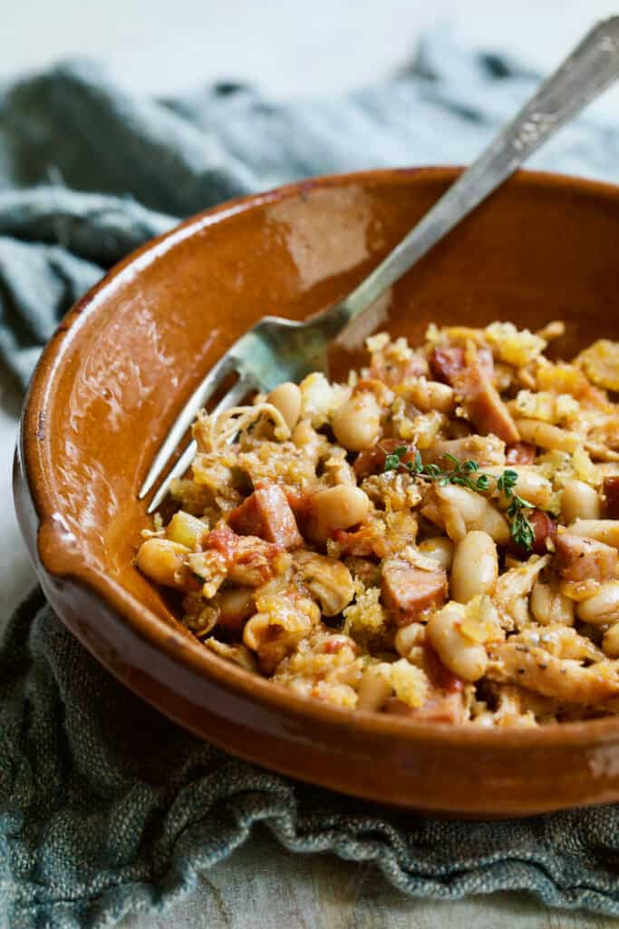 Photo of one serving of Easy Weeknight Chicken and Sausage Cassoulet in red clay bowl.