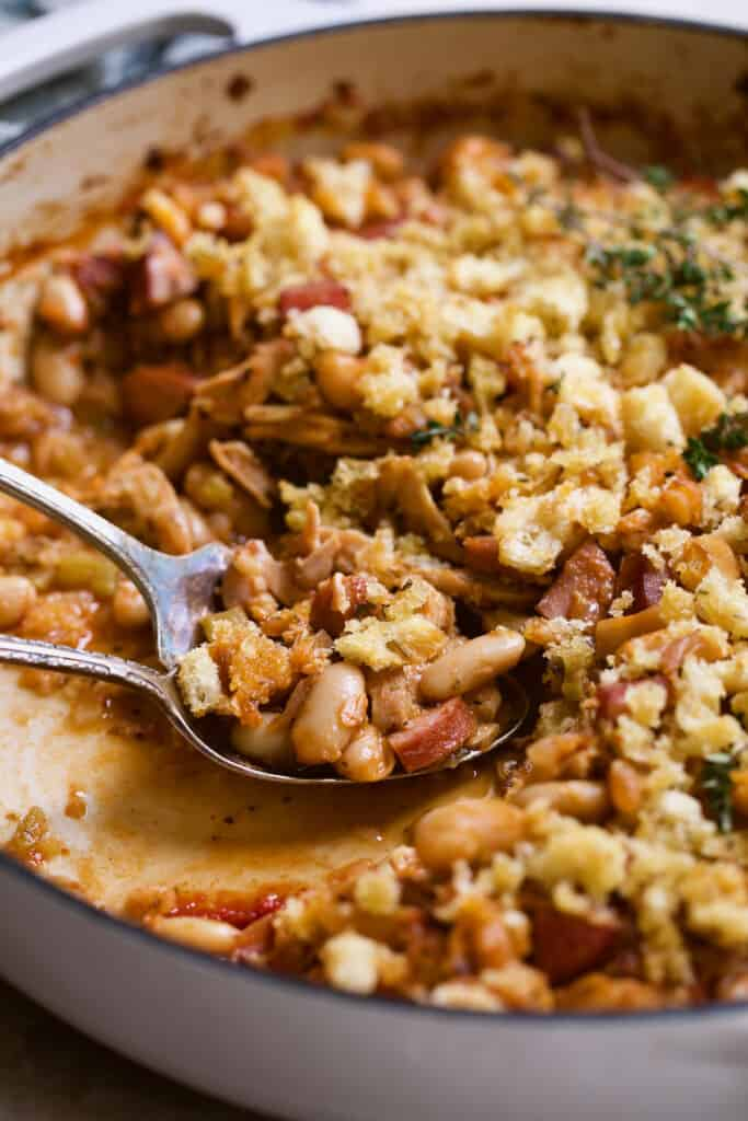 Close-up photo of cassoulet being served from white cast iron skillet.