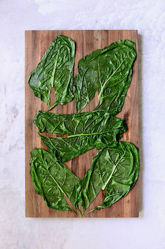 Photo of blanched Swiss chard leaves on wood cutting board.