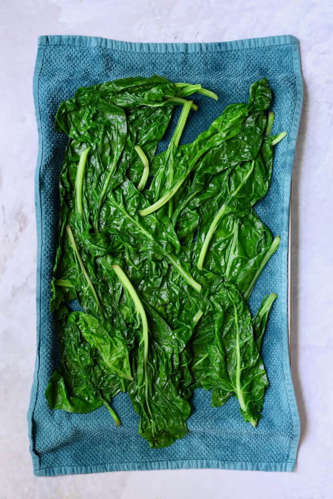 Photo of blanched Swiss chard leaves on blue towel.
