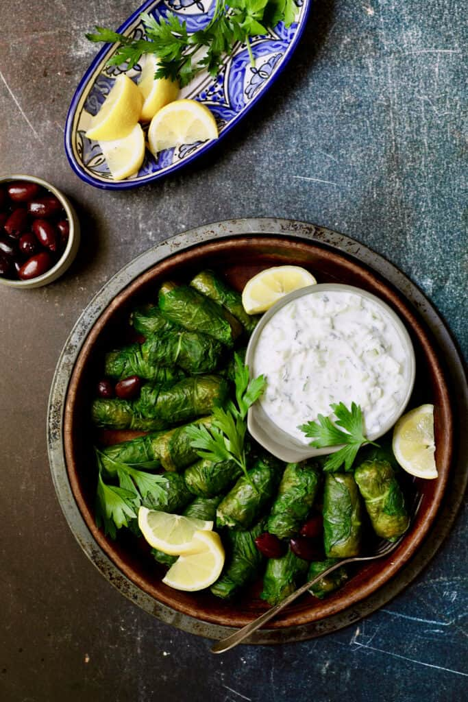 Photo of Swiss Chard and Quinoa Dolmas with Tzatziki with parsley sprigs.